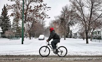 A cyclist makes his way along Mountain Avenue Sunday despite the snowfall. Roads are extremely slippery.