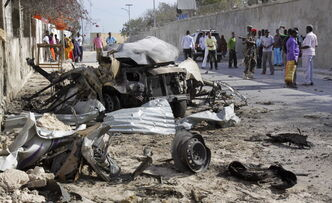 Somalis gather near the wreck of one of the vehicles militants used as a car bomb in an attack on the presidential palace.