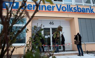 "Customers and a cameraman stand in front of a bank in Berlin Monday. German police say a 30-metre tunnel dug by robbers who raided the Berliner Volksbank was ""very professional"" and must have taken weeks or even months to complete."
