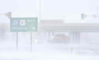 A plow clears snow off of Gateway Drive near I-29 in Grand Forks, N.D., as a blizzard moves through the Red River Valley.
