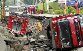 Rescue workers use a sniffer dog to look for missing persons believed to be buried as firetrucks lie damaged after massive gas explosions in Kaohsiung, Taiwan, Friday, Aug. 1, 2014. A series of explosions about midnight Thursday and early Friday ripped through Taiwan's second-largest city, killing scores of people, Taiwan's National Fire Agency said Friday. (AP Photo/Wally Santana)