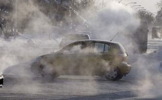 A car drives through exhaust fog this morning on McPhillips Street at Mountain Avenue
