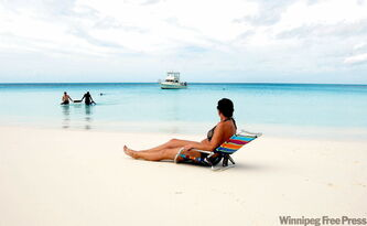 CNS-TRAV-BAHAMAS -- Kerry MacNaull lounges as the guys swim at Cape Santa Maria Beach in the Bahamas.