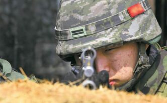 A South Korean marine peers down his machine-gun sight Friday as he trains to repel a possible North Korean attack.
