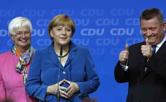 Secretary General Hermann Groehe (right) flashes two thumbs up as German Chancellor Angela Merkel (centre) waits to address supporters at the party headquarters in Berlin on Sunday.