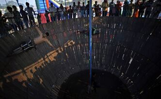 "In this Monday, Nov. 25, 2013 photo, an Indian performs stunts in a well of death at the elephant fair in Sonepur, India. Hoping there is something for everyone at this year's Sonepur Mela, organizers admit they are struggling to revive one of India's largest livestock markets now sapped of its main attraction by a ban on elephant sales. ""The mela is back to its old glamour,"" said Rahul, a local government official who goes by one name, running down attractions that include an exotic bird market, traditional folk music concerts, hundreds of street-food stalls and eight caged stages featuring writhing girls in heavy makeup and sparkly spandex. (AP Photo/Saurabh Das)"