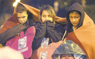 Brianna Blind, 13, Jenna Bates, 13, and Tianna Gomez, 12, keep warm at Thursday's vigil at the Manitoba legislature.