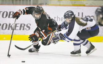 Shaftesbury Titans defenceman Cydnee Cook (right) is penalized for hauling down Sarah Potomak of Kelowna's Pursuit of Excellence team.