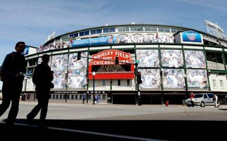 People walk by the marquee at Wrigley Field, one day before the Chicago Cubs' home opener against the Washington Nationals in Chicago. With the teams based in major cities; many of the stadiums are situated in bustling downtown areas with engrossing things to do and savory places to eat when you aren't attending a game.