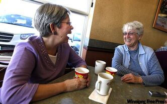 Cathy Kusheryk, (left) a Liberal, and friend Carol Trowski, a Conservative, talk politics Monday.