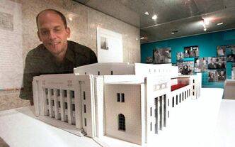 Andrew Kear, curator of The WAG Century exhibit, poses next to an architectural model of The Winnipeg Auditorium that opened in 1932. It became the second location of the Winnipeg Art Gallery.