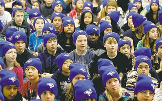 The kids listen intently to what the three visiting Blue Jays tell them.