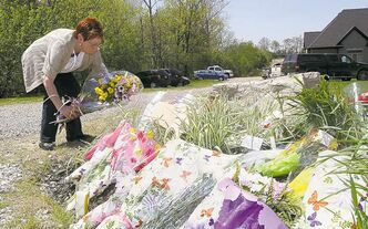 A woman places flowers in front of Tim Bosma's home in Ancaster, Ont.
