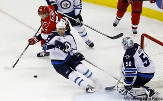 The Carolina Hurricanes' Jeff Skinner (53) tries to score as Winnipeg Jets' Randy Jones and goalie Chris Mason defend during the third period of their NHL game in Raleigh, N.C., Monday. Carolina won 2-1.