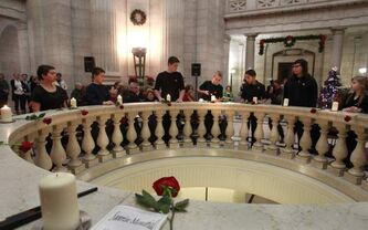 David Brinkman (centre) lights a candle at a Sunrise Memorial Ceremony at the Legislative Building.