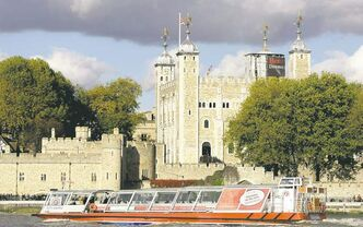 A leisure boat on the Thames river passes passes the Tower of London.