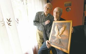 Pedro Pontanilla, with longtime friend, Jaime 'Hymie' Carrasco, holds the copper engraving of the Chilean condor he made after being  imprisoned for  opposing the military coup of Augusto  Pinochet.