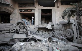 A Palestinian man walks next to a destroyed house following an overnight Israeli missile strike in Gaza City.