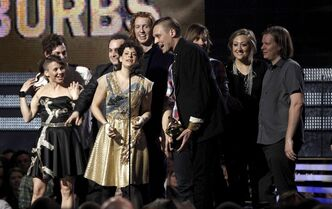FILE - Regine Chassagne, center left, and Win Butler, center right, are joined by fellow band members of Arcade Fire to accept the award for album of the year at the 53rd annual Grammy Awards on in this Feb. 13, 2011 file photo taken in Los Angeles. Arcade Fire is the top nominee for the 2014 mtvU Woodie Awards. The Montreal-based band has three nominations for the March 13, 2014 awards show celebrating music embraced by college students (AP Photo/Matt Sayles, File)