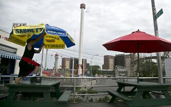 The Astrotower, center, a landmark of Coney Island amusement park, looms in the background as a worker setup tables on the boardwalk on Wednesday, July 3, 2013 in New York. The park remains closed while workers examine the condition of the 275-foot-tall observation Astrotower. The park was evacuated on Tuesday after the fire department received a call that the tower was swaying. (AP Photo/Bebeto Matthews)