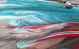 Charlie Johnston works on his 4,000-square-foot 3D chalk art drawing.