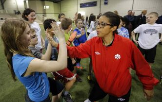 Desiree Scott, member of Canadian women's national team and Olympic bronze medallist, gives high-fives to Grade Six students from Edmund Partridge Community School. Provincial, city and soccer association officials were on hand to announce funding for a new FIFA-sized indoor soccer facility in north Winnipeg.