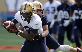Derek Jones, right, hauls down Mario Urrutia during a practice at Investors Group Field this season.