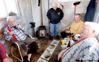 Fred Sokolosky, second from right, relaxes with his buddies in their ice-fishing shack near Selkirk.
