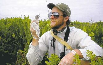 Bryce Hoye, on Country Island, N.S., in 2010, examines a bird he came across in his field biology work.