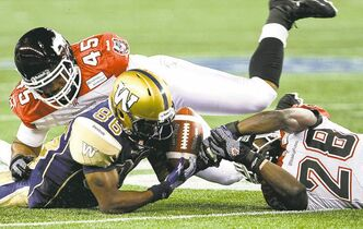 Isaac Anderson (#86) and Brandon Smith (#28) struggle for control of the ball, but fumble. The Winnipeg Blue Bombers faced off against the Calgary Stampeders at home on Friday, July 26, 2013. (JESSICA BURTNICK/WINNIPEG FREE PRESS)