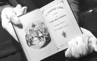 An employee at Sotheby's holds an 1843 first edition of the classic A Christmas Carol by Charles Dickens.