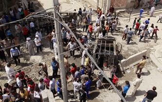 Civilians gather at the scene of a car bomb attack in the east Baghdad neighborhood of Kamaliya, Iraq, Monday, April 15, 2013. Less than a week before Iraqis in much of the country are scheduled to vote in the country's first elections since the 2011 U.S. troop withdrawal, a series of attacks across Iraq, many involving car bombs, has killed and wounded dozens of people, police said. (AP Photo/ Khalid Mohammed)