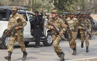 Pakistan army soldiers rush to the scene of a bombing in Peshawar, Pakistan on Monday, Feb. 18, 2013. Militants wearing suicide vests and disguised as policemen attacked the office of a senior political official in northwestern Pakistan on Monday, killing many people, police and hospital officials said. (AP Photo/Mohammad Sajjad)