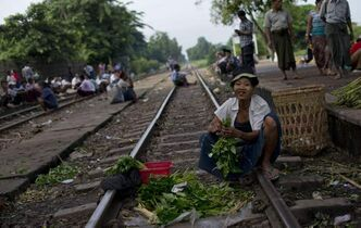 A vegetable vendor sits in a railway track and clean green leafs near a railway station platform in suburbs of Yangon, Myanmar.