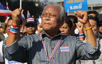 Thai anti-government protest leader Suthep Thaugsuban raises clenched fists during a march with his supporters in Bangkok on Monday. Anti-government protesters took over key intersections in Thailand's capital , halting much of the traffic into Bangkok's central business district as part of a months-long campaign to thwart elections and overthrow the democratically elected prime minister.