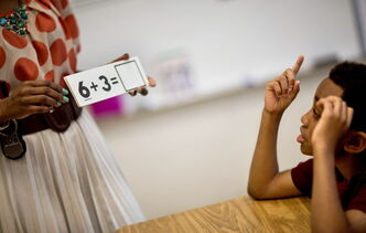 Burgess-Peterson Elementary School second grader Carl Hood (right) sits through a lesson with instructor Lola Onikoyi as part of Atlanta Public School's after-school remediation program in Atlanta.