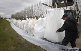 Dave Hofer guides a massive sandfilled bag into place along the main road into the Starlite Hutterite Colony close to Starbuck.
