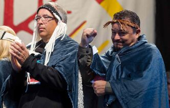 National Chief Shawn Atleo (right) of the Assembly of First Nations, pumps his fist while standing with B.C.Aboriginal Relations and Reconcilliation Minister John Rustad during the Walk for Reconciliation in Vancouver, B.C., on Sunday. Thousands of people attended the walk that wrapped up a week Truth and Reconciliation Commission of Canada events in the city.