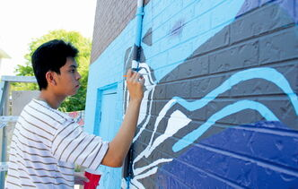 Christian Mariano, 18, colours in the fine details of a totem pole as part of a mural going up on the side of the 7-Eleven at Mountain Avenue and McPhillips Street on July 4.