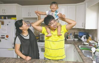 Jerry Jiang and his wife, Yuyan Liu, play with their 16-month-old son Ethan. When Jiang first came to Manitoba in 2008 to work at Maple Leaf Foods in Brandon, he only planned to stay for two years.