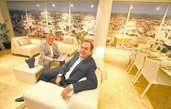 Realtor Gary Bachman (left) and Creswin's Dan Edwards relax in a condo display suite for One Portage & Main.