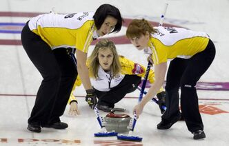 Jennifer Jones, centre, makes a shot as second Jill Officer, left, and lead Dawn Askin sweep during the game against Alberta at the Scotties Tournament of Hearts in Red Deer.