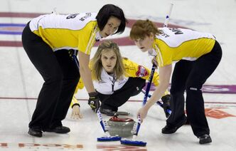 Manitoba skip Jennifer Jones, centre, makes a shot as second Jill Officer, left, and lead Dawn Askin sweep during a afternoon draw against Alberta at the Scotties Tournament of Hearts in Red Deer, Alberta, Sunday.