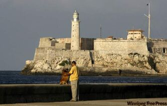 A man walks his dog at the Malecon in Havana.