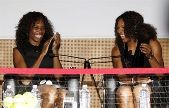 Venus Williams, left, and her sister Serena, of the United States, smile during a press conference to present Saturday's exhibition match against Italy's Flavia Pennetta and Francesca Schiavone in Milan, Italy, Friday, Dec. 2, 2011. (AP Photo/Antonio Calanni)