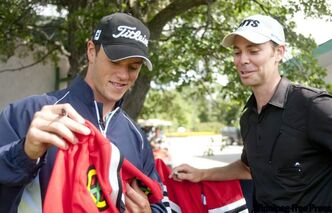 Jonathan Toews (left) autographs a hockey jersey for Canadian Tour's Adam Speirs while making rounds to meet Players Cup team members at Pine Ridge.
