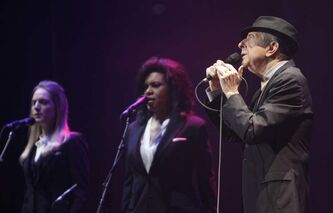 Leonard Cohen (seen here with two of his backup singers) delivers a moving performance at the MTS Centre Friday.
