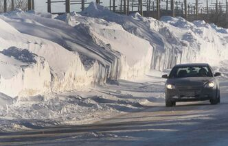 A car drives on Saskatchewan Avenue in St. James, dwarfed by massive snow banks nearly four metres high.