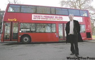 Dawkins poses for photographers in front of a London bus featuring an atheist advertisement with the slogan 'There's probably no God. Now stop worrying and enjoy your life'.
