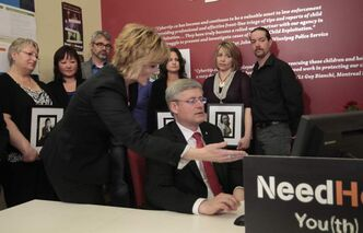 Prime Minister Stephen Harper at a computer with Cybertip.ca's Signy Arnason, surrounded by cyberbulling victims' families.